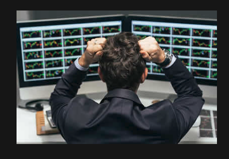 Impatient Trader sitting at his desk pulling at his hair.